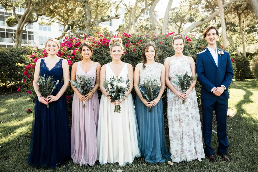 bridesmaids in mismatched bhldn bridesmaid dresses holding greenery bouquets