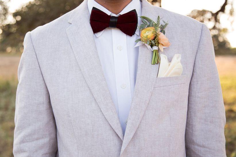 groom light suit white button down burgundy bow tie cream pocket square ranunculus boutonniere