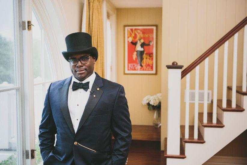 groom navy jacket black lapels black bow tie black top hat gold hardware