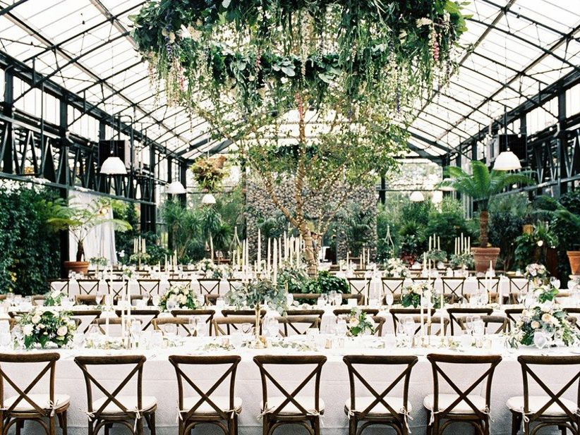 romantic conservatory wedding venue in Michigan with greenery chandeliers and sky lights