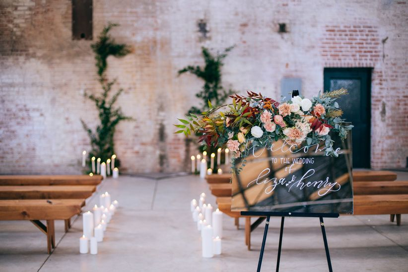 modern romantic wedding ceremony altar with brick wall decorated with mirror signage, greenery and candles