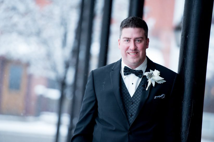 Groom winter attire black tux checkered vest bow tie and pocket square white floral boutonniere