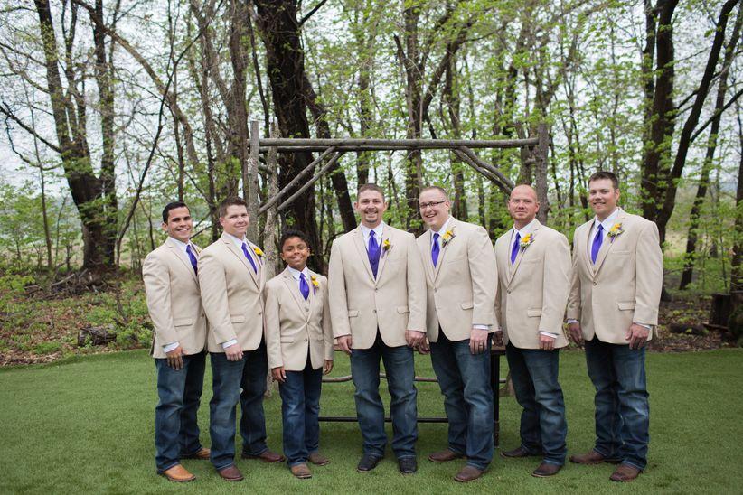 groom and groomsmen tan jackets dark wash jeans vibrant purple ties boutonnieres outdoors