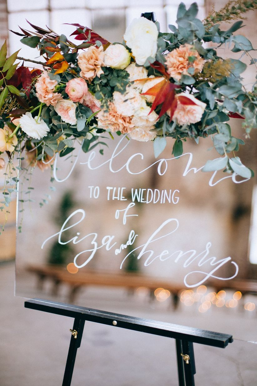 modern wedding welcome sign with calligraphy written on mirror decorated with blush flowers and greenery