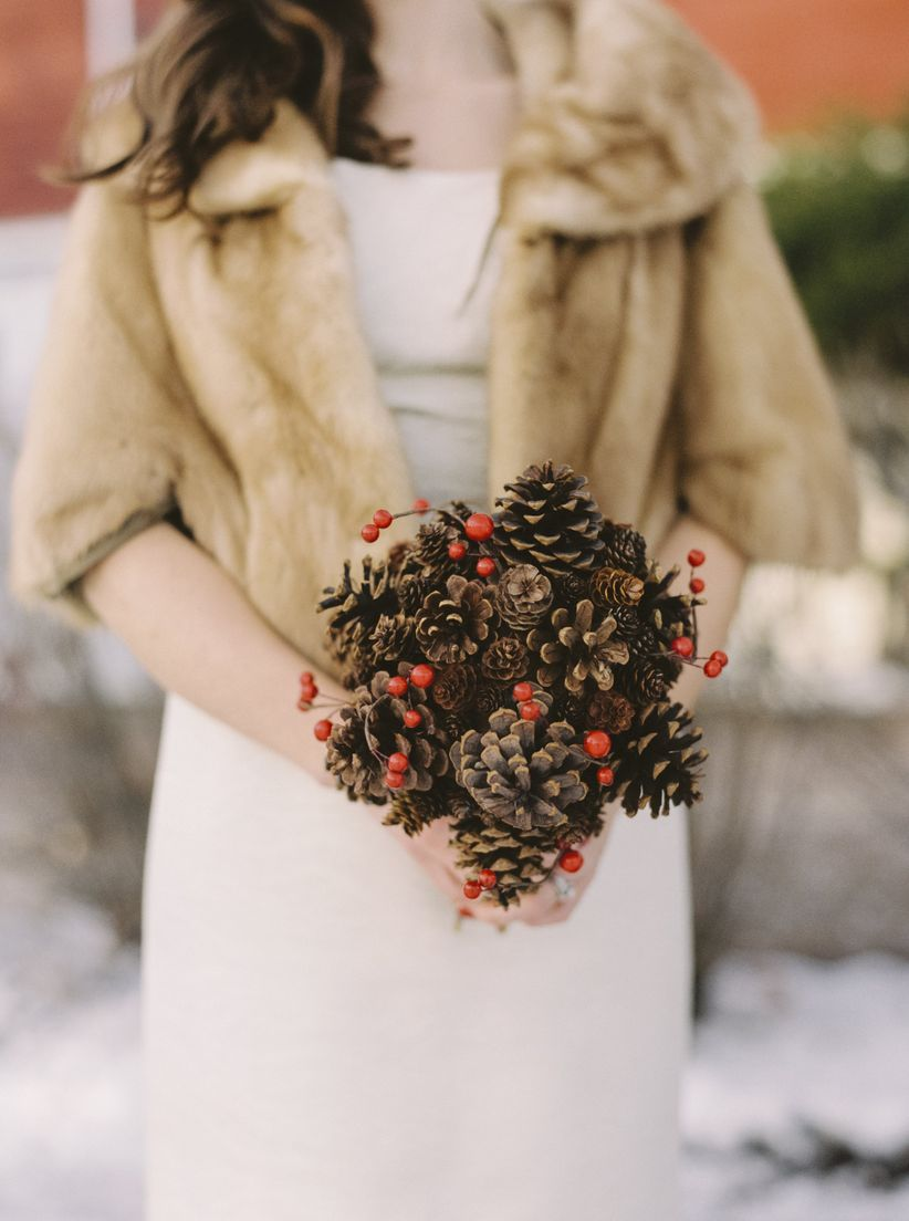 women in winter wedding attire holding a bouquet of pine cones and hypericum berries