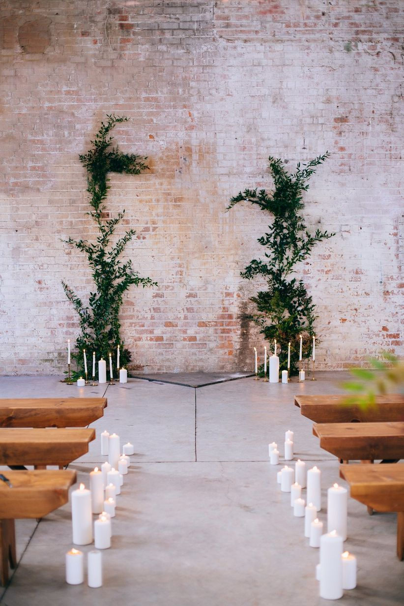 industrial warehouse wedding venue with brick wall decorated with candles and greenery vines