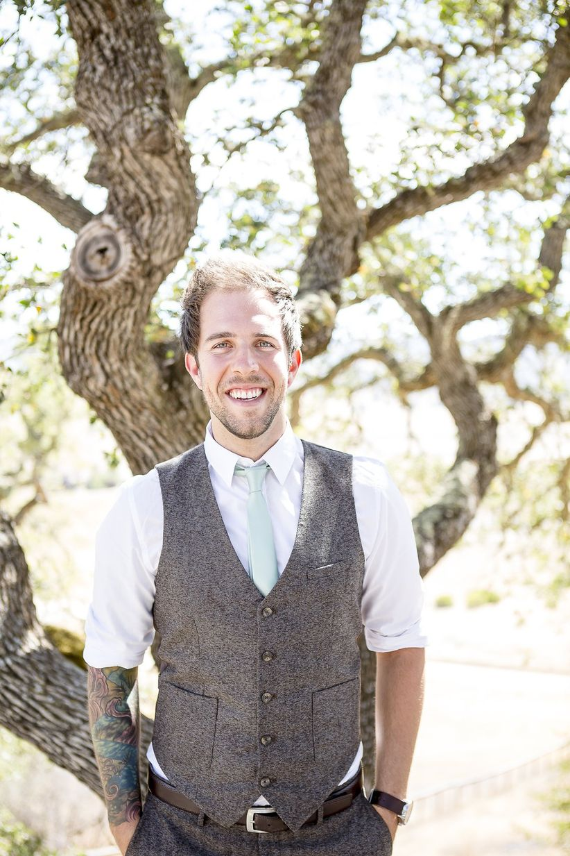groom in tweed vest and pants with white button down rolled up sleeves mint green necktie