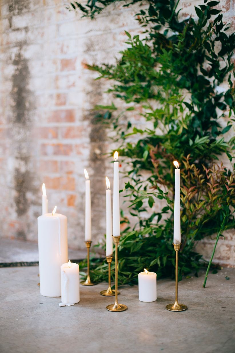 romantic wedding ceremony decor with white candles and greenery