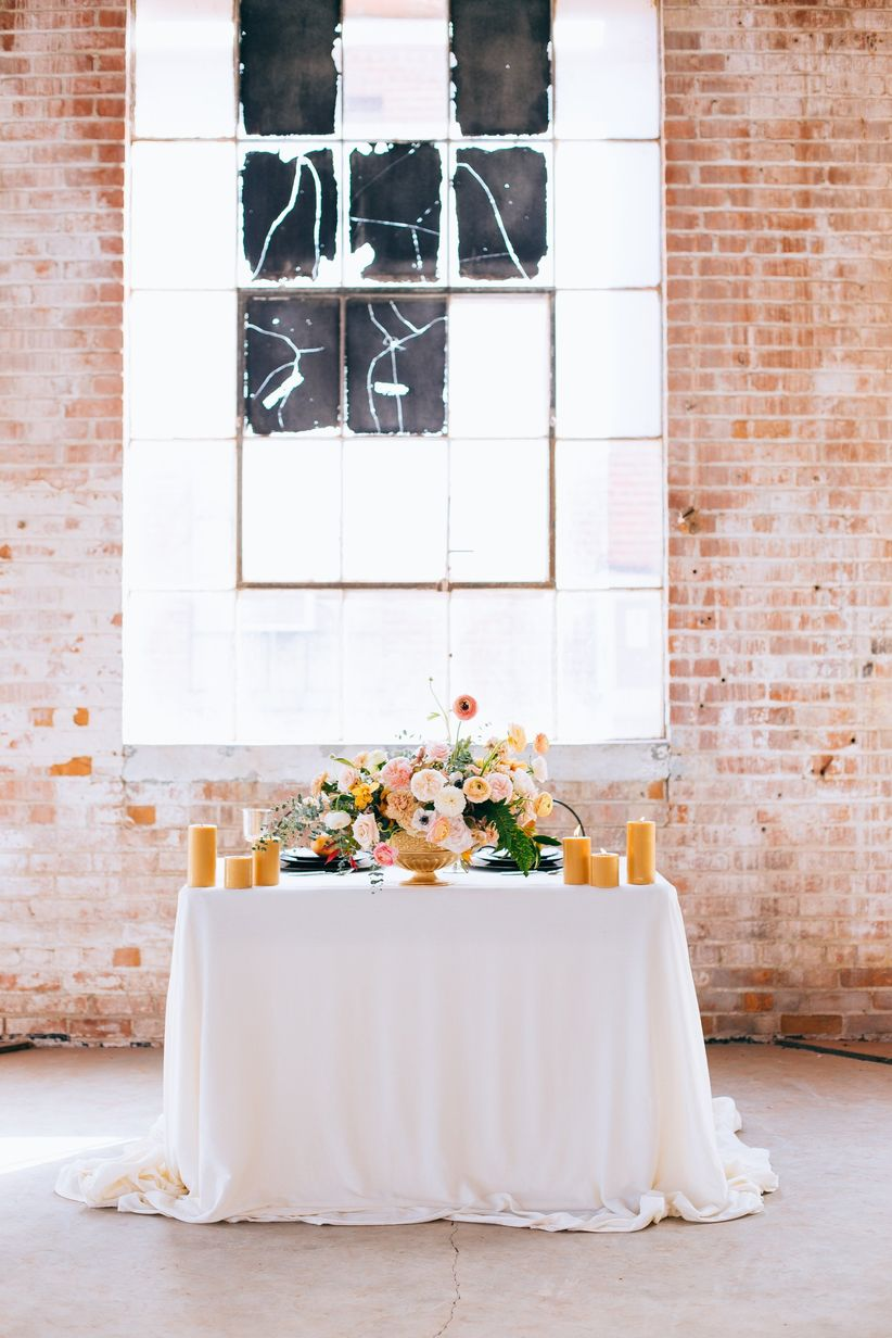 wedding reception table at industrial warehouse wedding venue with blush and peach flower centerpiece