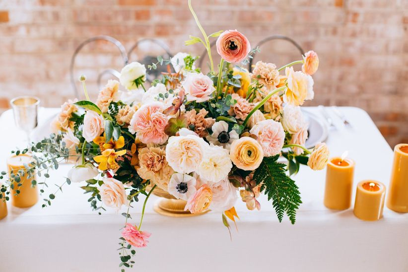 romantic blush and peach centerpiece with garden roses, ranunculus, anemones, greenery