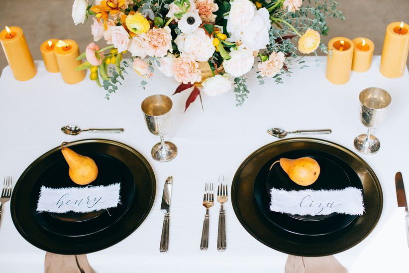 modern place setting idea with black chargers and pear place cards with calligraphy