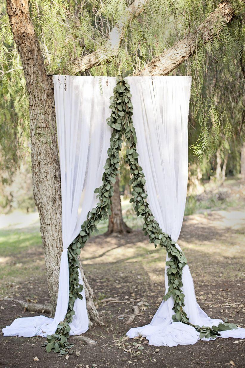 DIY ceremony backdrop with greenery garland