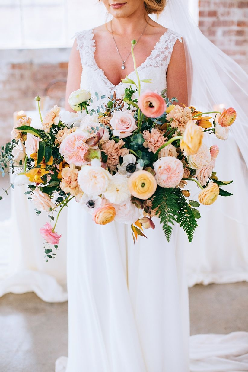 blush and peach wedding centerpiece with garden roses, ranunculus, carnations and greenery