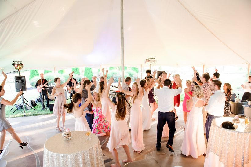 wedding guests dancing with hands raised in the air