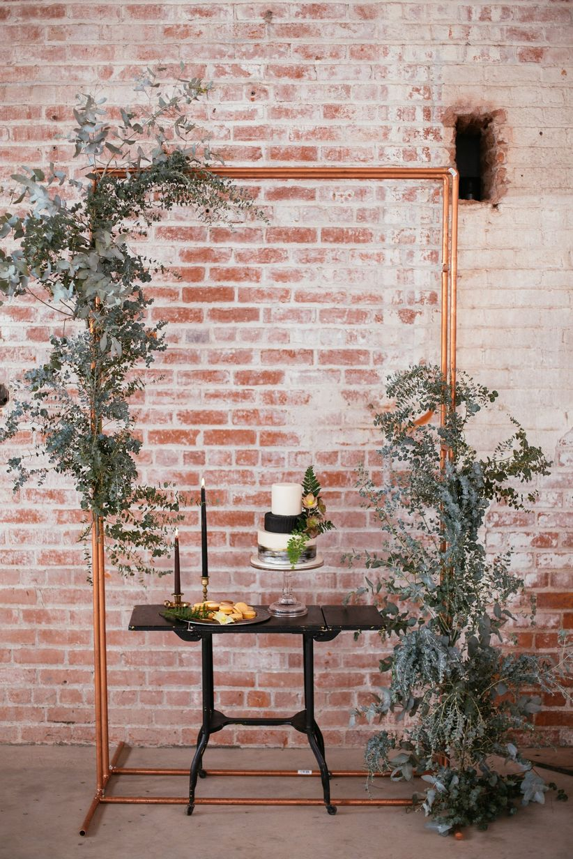 industrial venue with modern wedding cake display decorated with greenery and copper backdrop