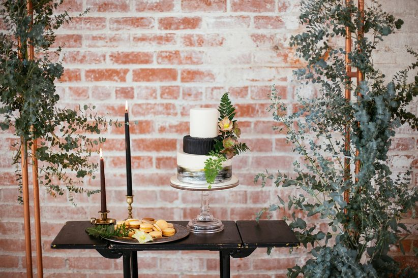 modern wedding cake table decorated with copper frame and greenery