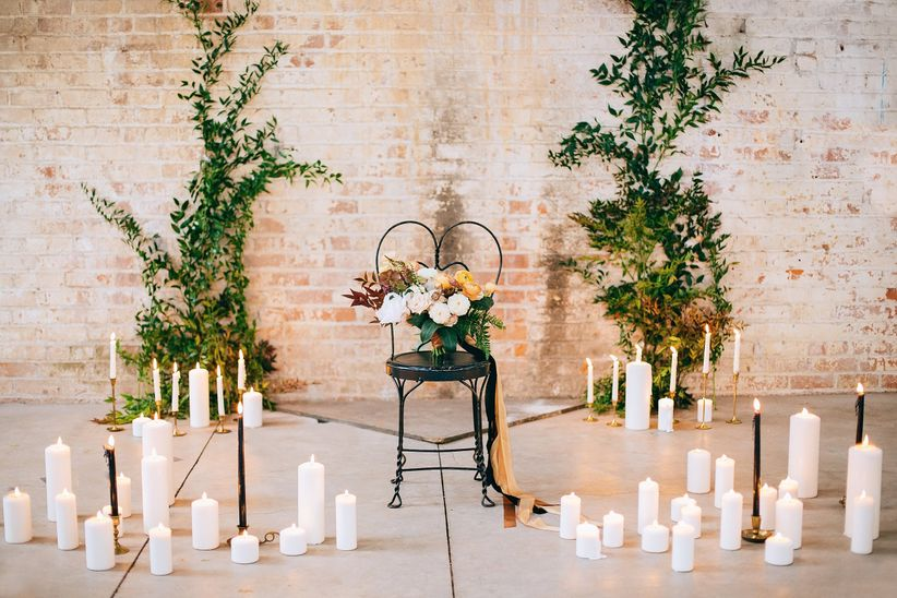 modern romantic wedding ceremony altar idea with clusters of white candles and greenery against a brick wall