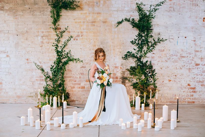 bride sits at indoor wedding venue in front of romantic wedding ceremony backdrop with candles and greenery