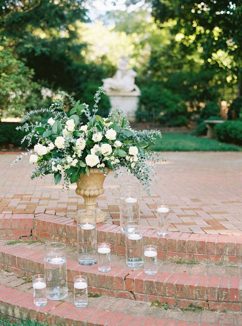 romantic garden wedding ceremony decor with potted roses and floating candles