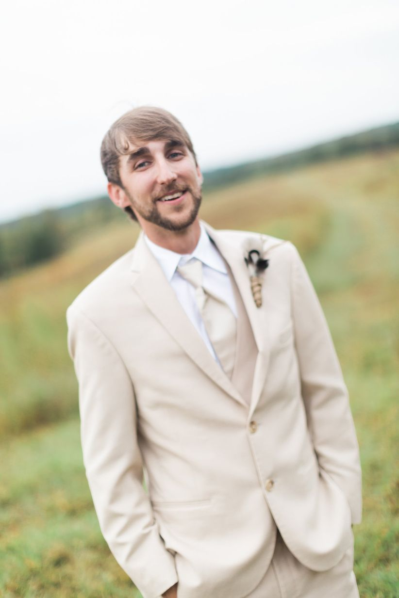 groom in tan three piece suit with matching tie white button down rustic boutonniere