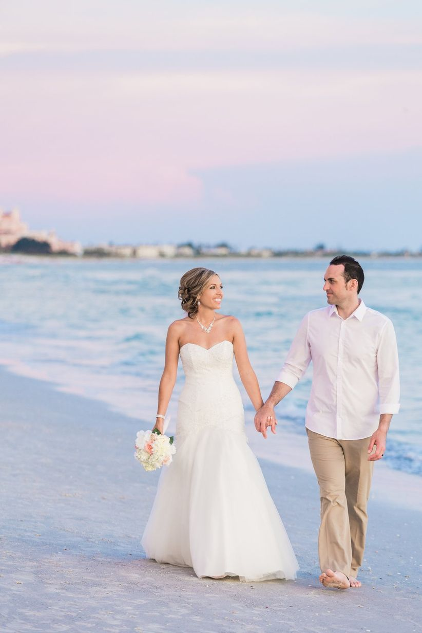 bride and groom walking down beach groom in white button down rolled sleeves khaki pants and bare feet