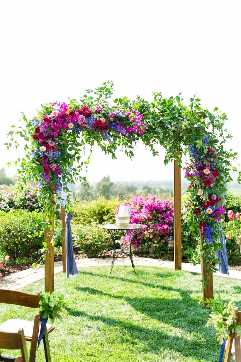 bright pink and purple greenery ceremony structure
