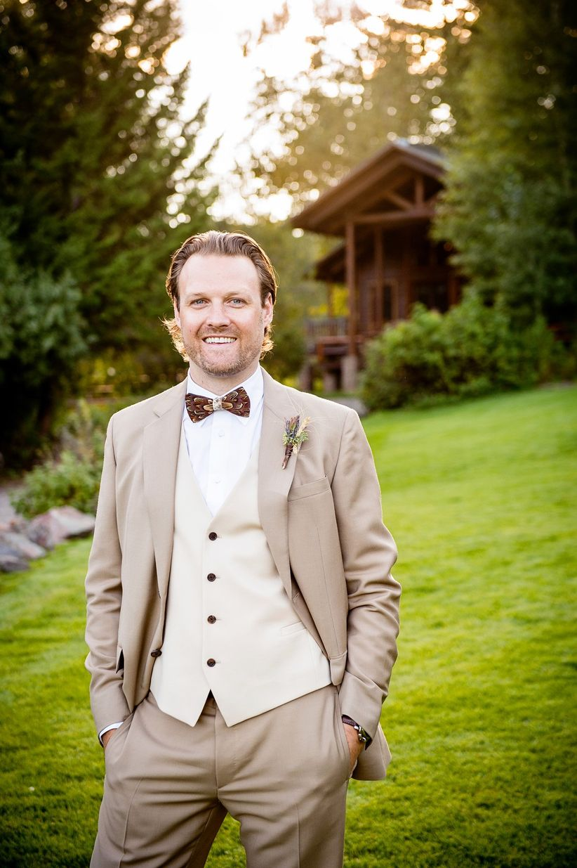 rustic groom brown suit tan vest feather bow tie wild flower boutonniere