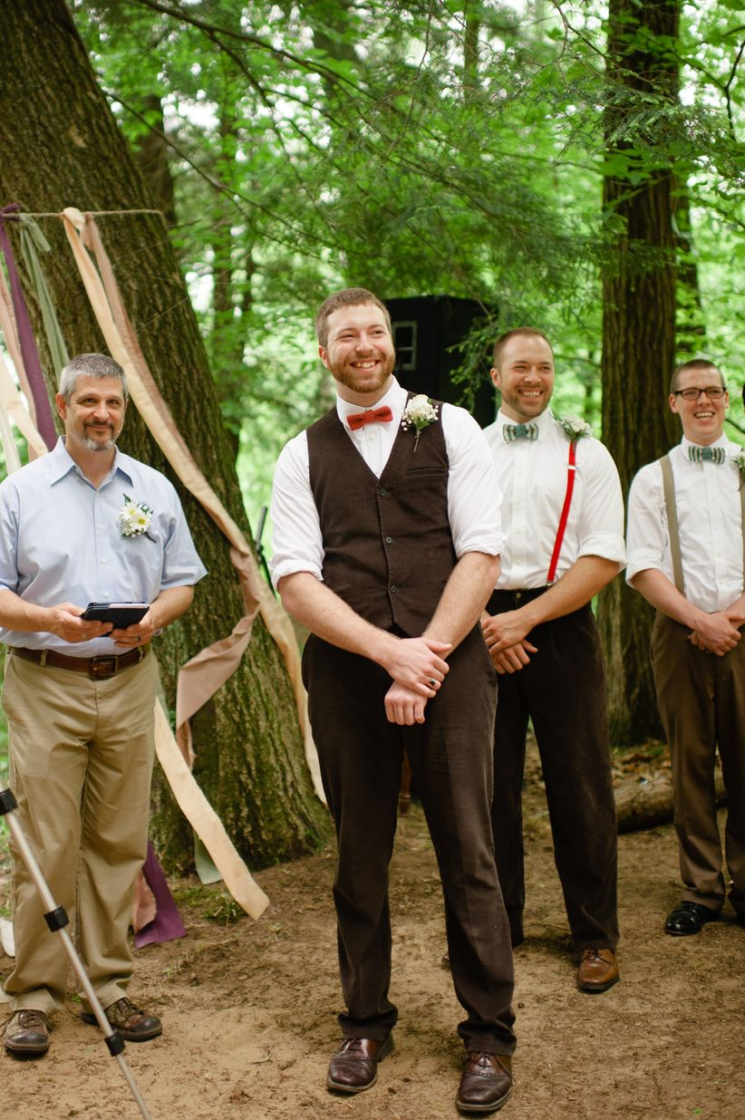 outdoor ceremony groom in white button down rolled sleeves brown vest and matching pants red bow tie