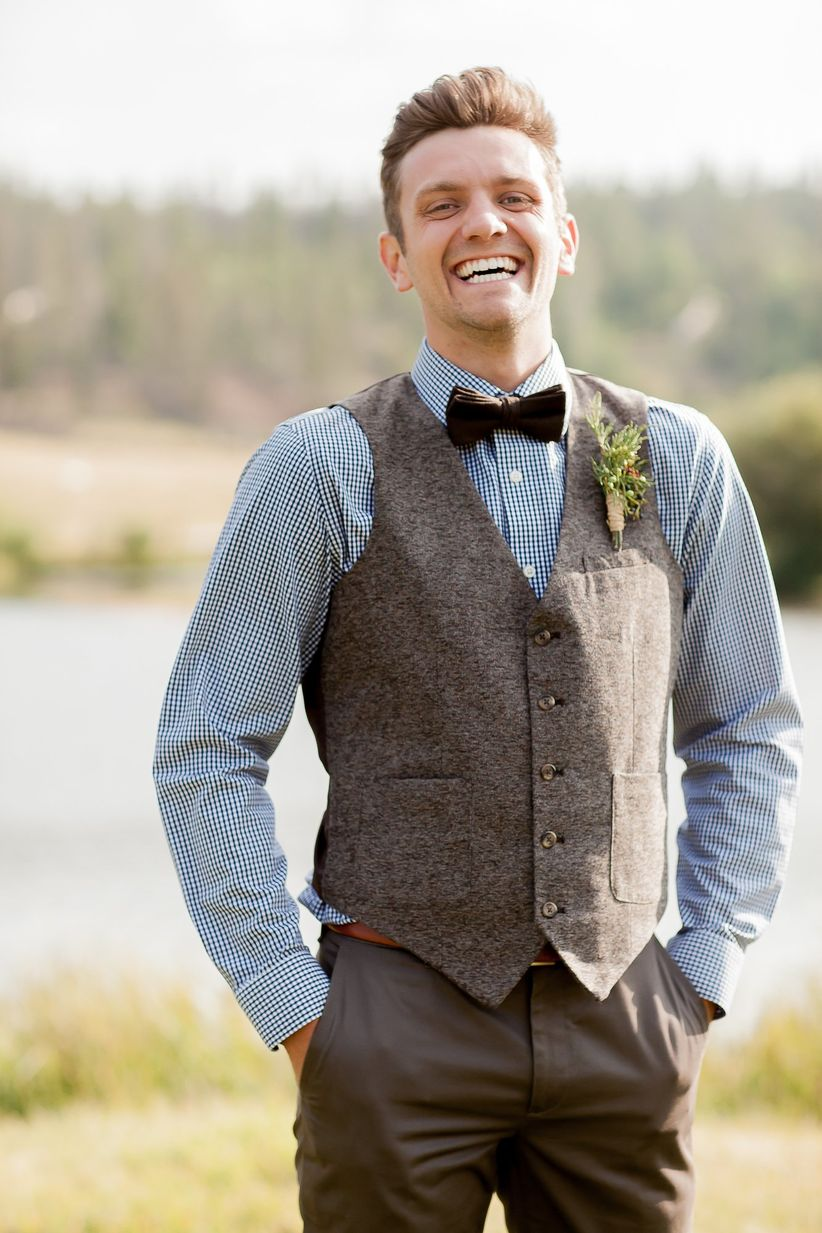 rustic groom in tweed vest with blue and white checkered button down brown velvet bow tie and greenery  boutonniere