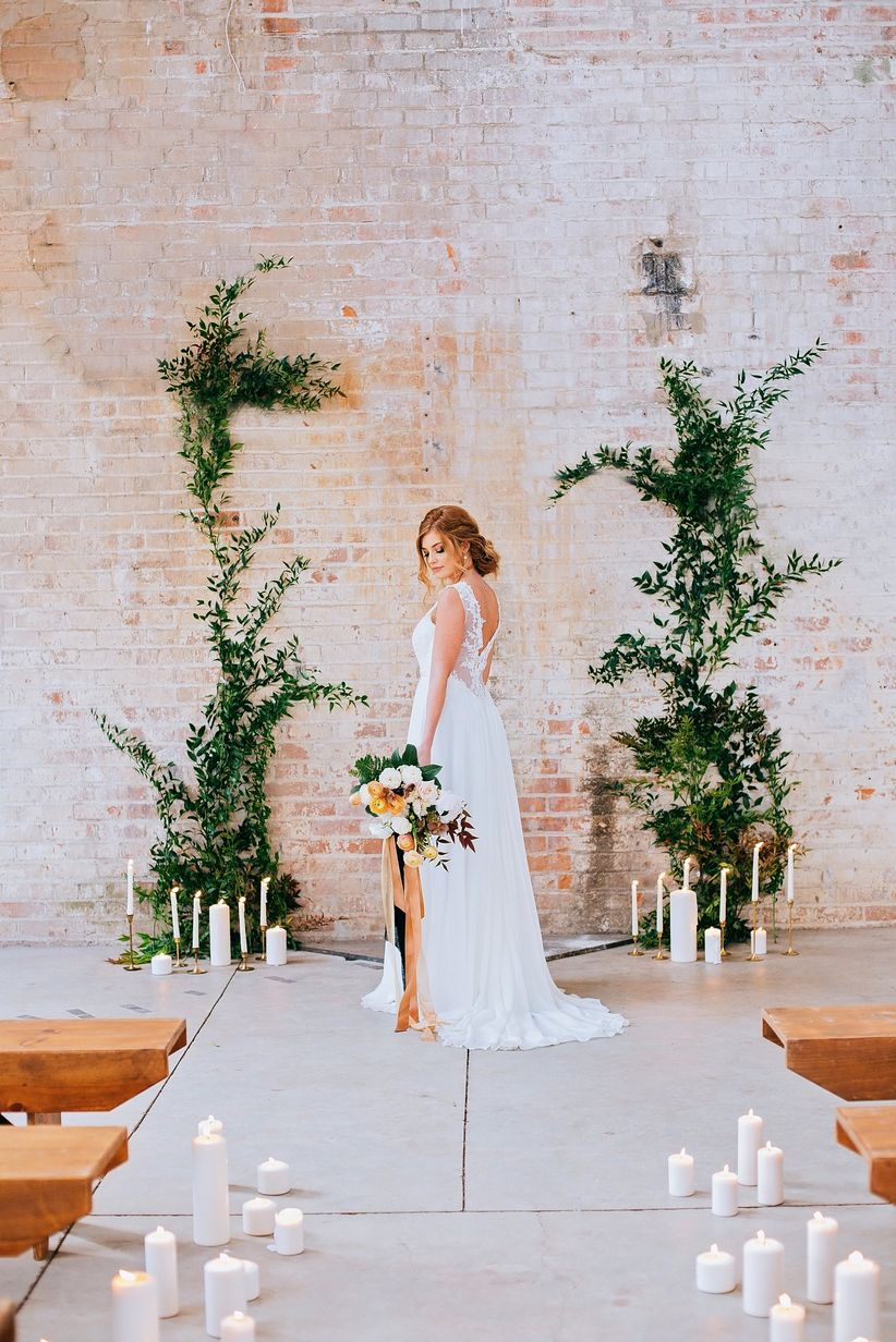 bride wearing romantic loose wedding dress with low back stands at industrial ceremony altar with greenery and candles