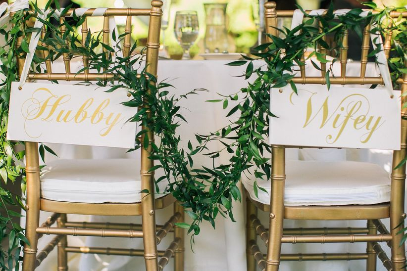 chiavari chairs with greenery and signs