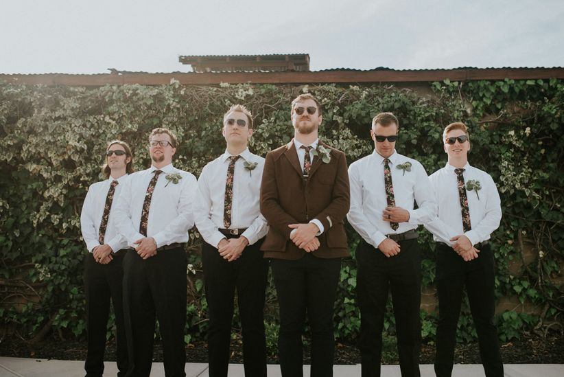 groom and groomsmen white button down black pants thin black floral tie groom in herringbone jacket
