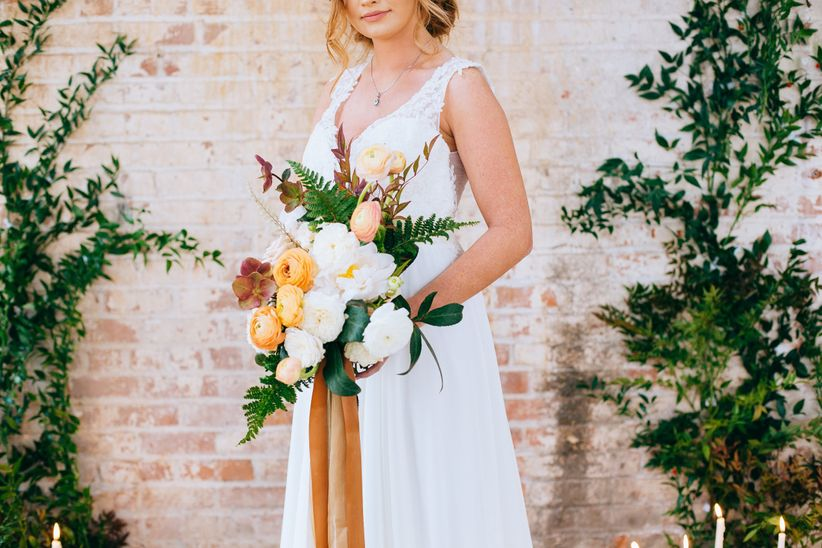 modern romantic wedding bouquet with white garden roses yellow ranunculus hellebores and greenery