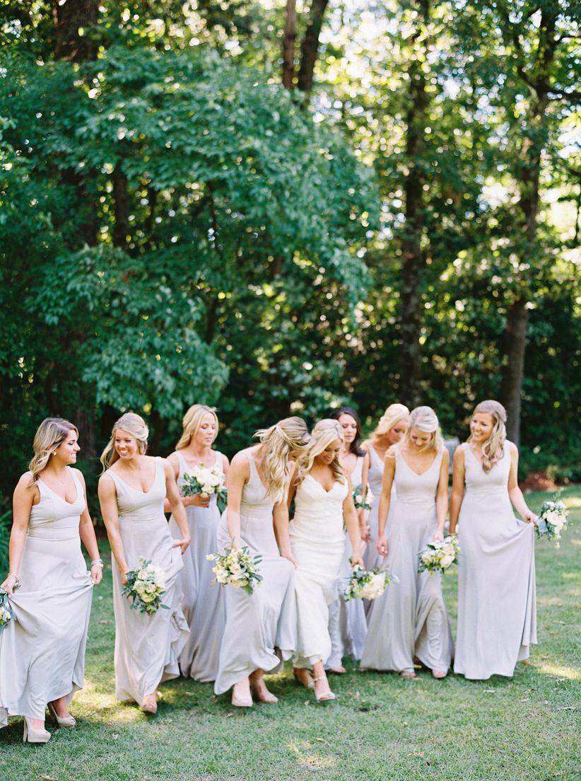 bridal party wearing long blue bridesmaid dresses at elegant garden venue