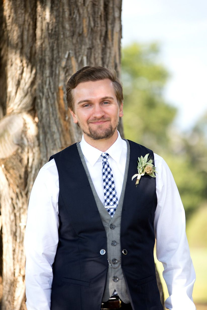 groom in layered vest with blue checkered tie white button down boutonniere with scabiosa pod and greenery