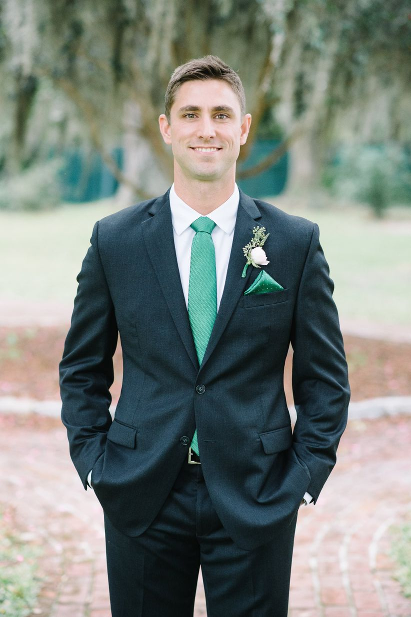 Groom in dark navy suit emerald green tie and matching pocket square with polka dots floral boutonniere