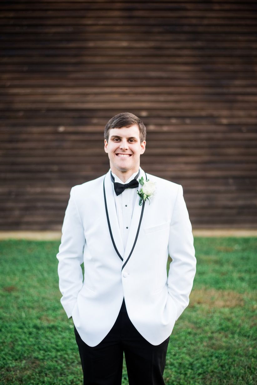 southern groom white tux jacket with black piping black slacks bow tie white floral boutonniere