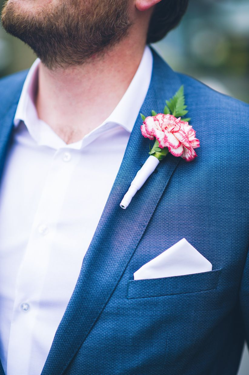 groom in navy suit with light pastel button down matching pocket square and carnation boutonniere