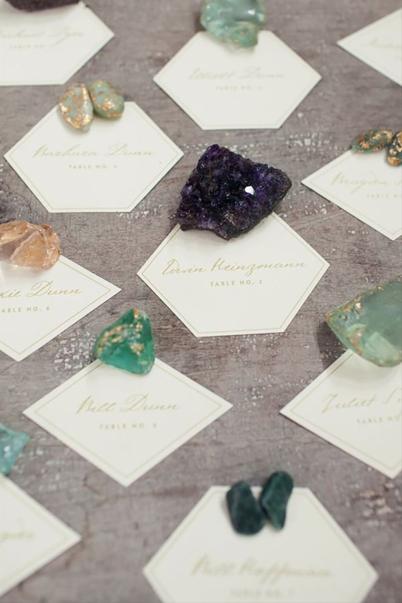 bohemian wedding escort cards in geometric shapes decorated with raw crystals and gemstones