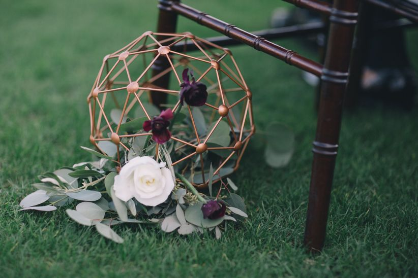 winter wedding aisle marker with gold geometric sphere, burgundy flowers and greenery