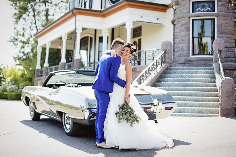 couple posing by vintage car