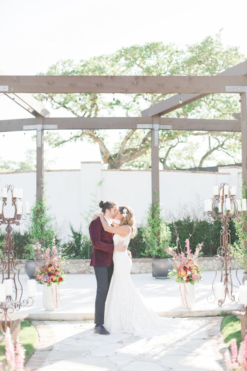 outdoor wedding ceremony in a garden with wooden arbor and colorful flower aisle markers