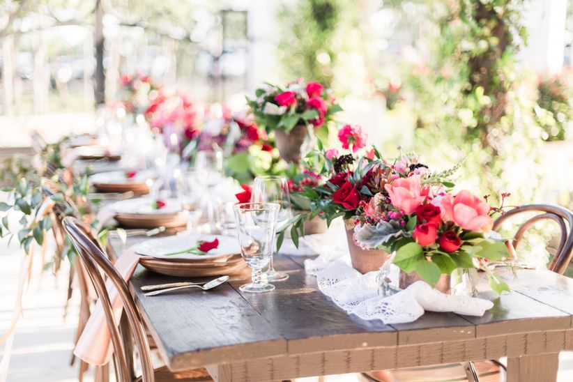 long wedding table decorated with low centerpieces of pink and red flowers with greenery