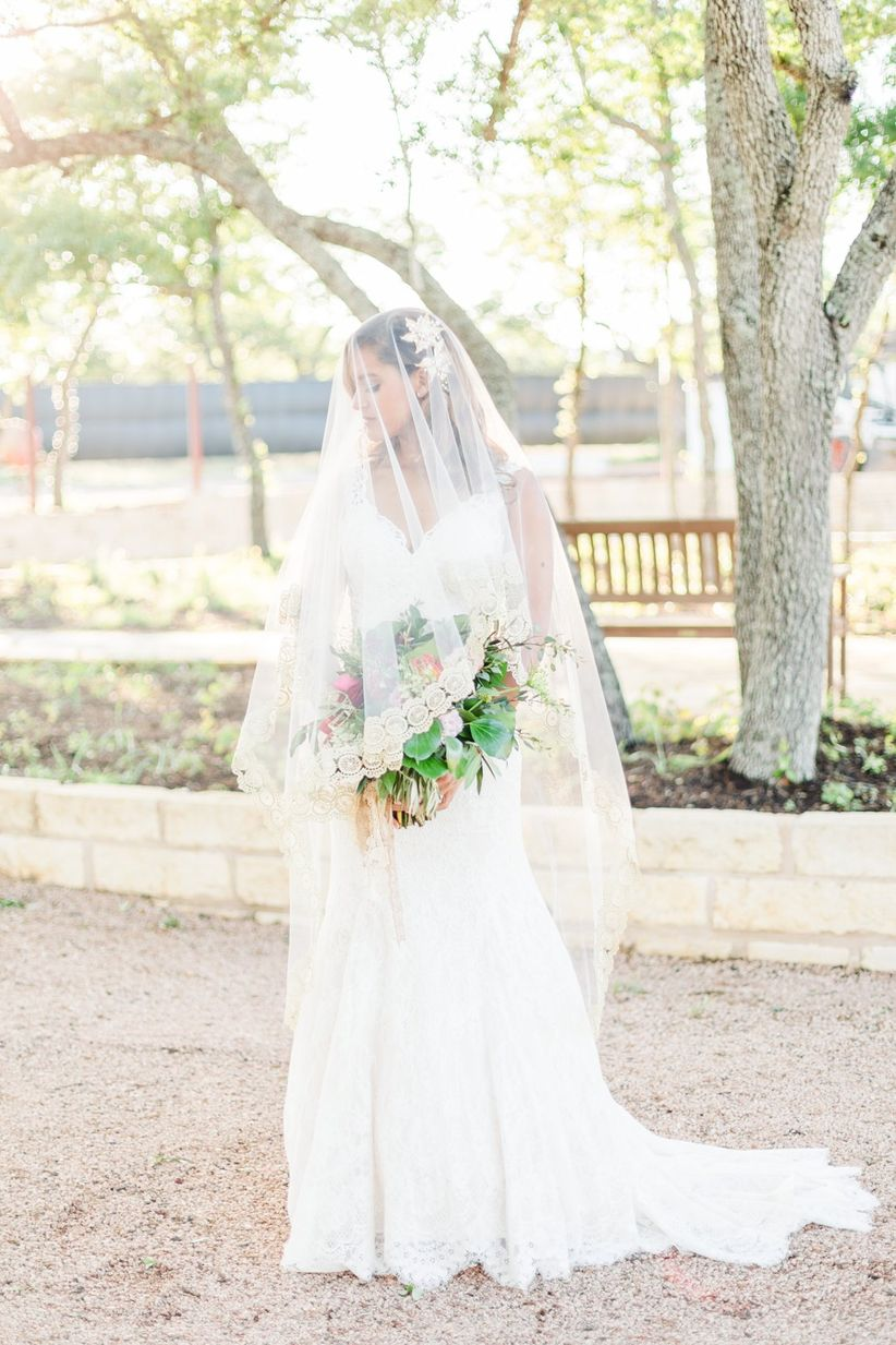 bride wearing elegant classic veil and lace wedding dress with chapel train