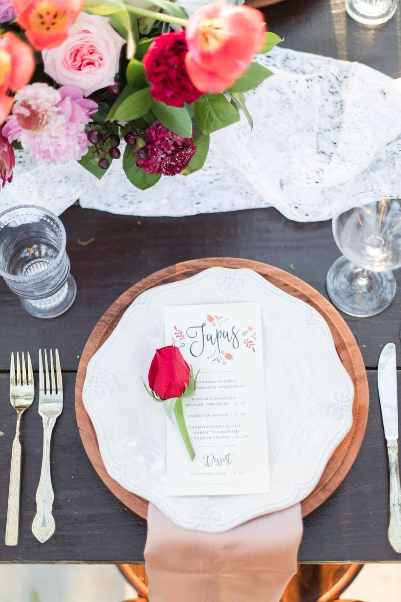 romantic wedding place setting decorated with tapas menu card and single rose bud