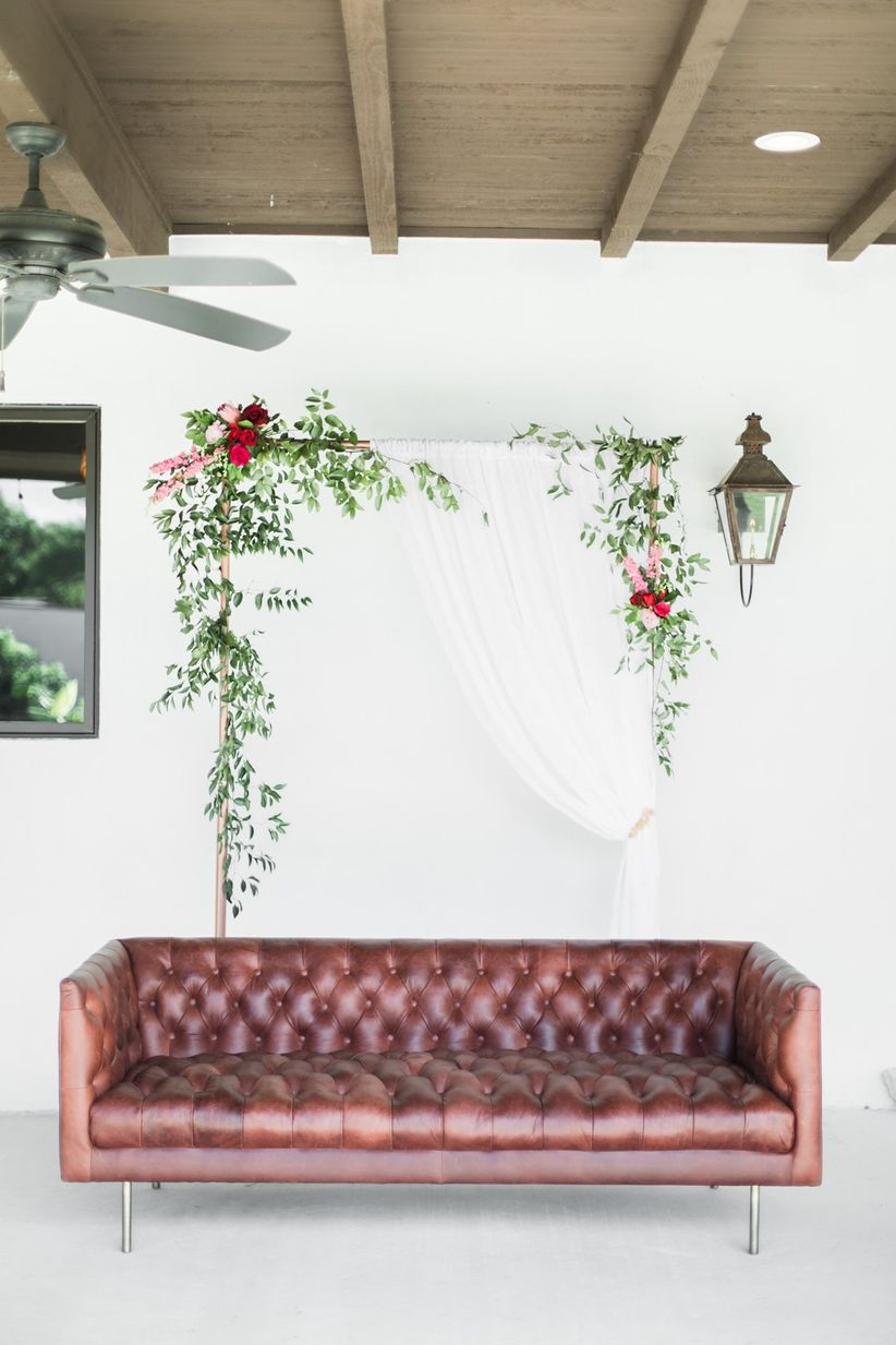 romantic wedding lounge idea with vintage maroon leather couch and white fabric backdrop decorated with greenery and pink flowers