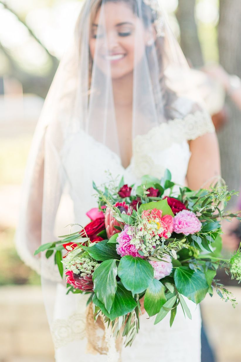 colorful wedding bouquet with pink and red flowers surrounded by fresh greenery