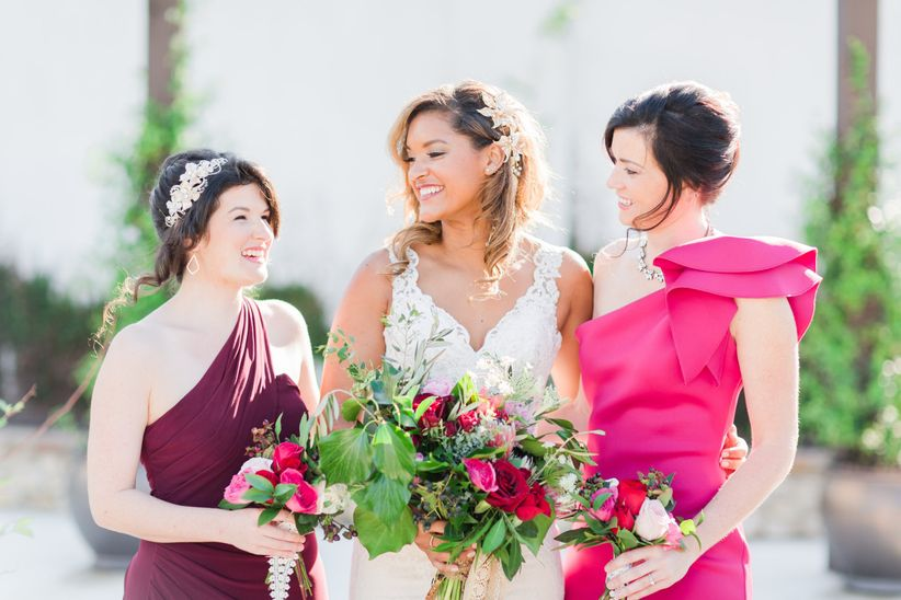 bride posing with bridesmaids wearing bright pink and burgundy bridesmaid dresses