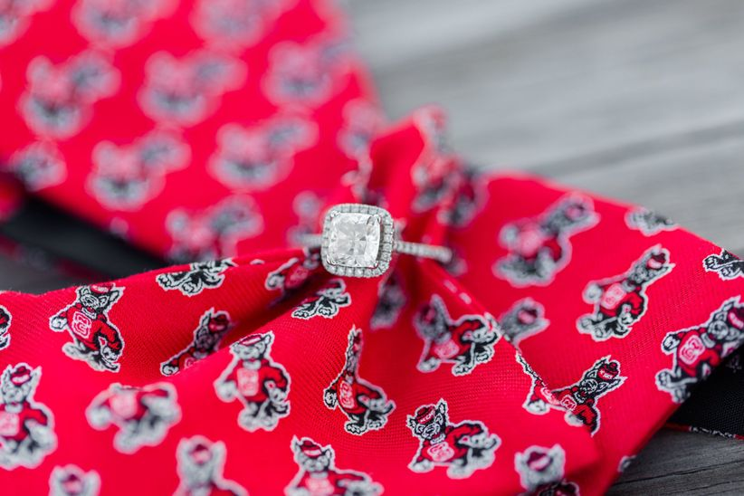 Cushion cut halo engagement ring on red tie