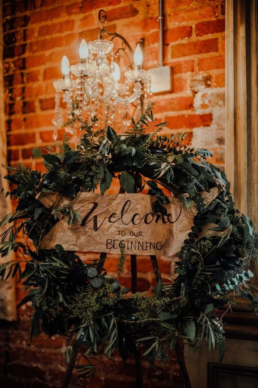 modern wedding welcome sign decorated with greenery wreath